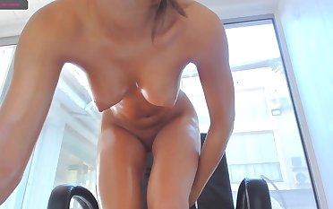 Teenage with oiled body pleases her vagina with a dildo